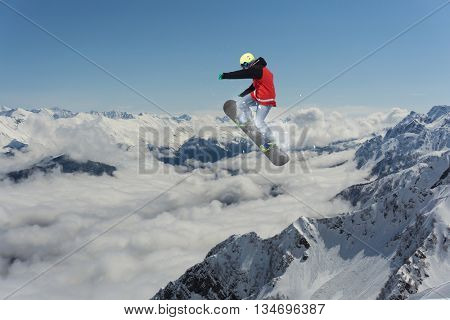 Snowboarder making high jump in cloudy sky.