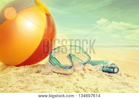 Beach ball and goggles in the sand at the beach