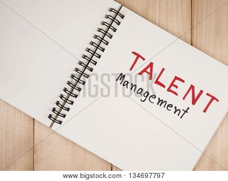 Handwriting Talent Management on blank notebook with wood background. (Business concept)