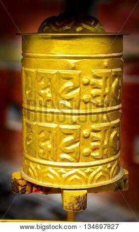 Yellow coloured Prayer Wheel photographed in Kathmandu Nepal.