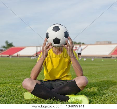 Boy Sitting On The Grass In A Football Stadium, And Holds A Soccer Ball In Front Of Him