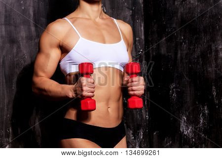 Strong woman with red barbells