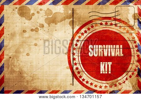 Survival kit sign, red grunge stamp on an airmail background