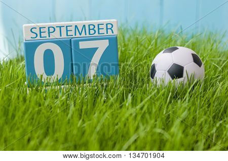 September 7th. Image of september 7 wooden color calendar on green grass lawn background. Autumn day. Empty space for text.