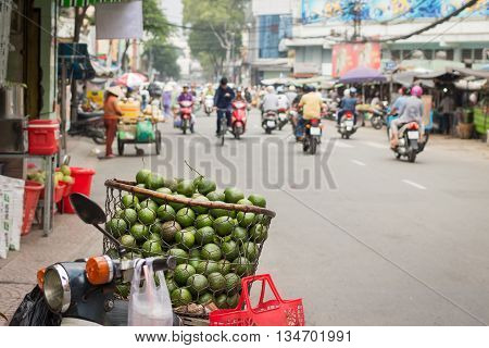 Vietnamese street hawker with a basket full of sweet oranges on bike in Ho Chi Minh city.