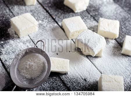 Honey marshmallows with sugar powder on a black background. The jar with marshallows on back.
