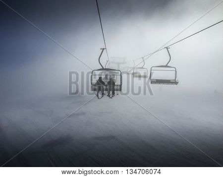 Two people riding a chair atop a snow mountain