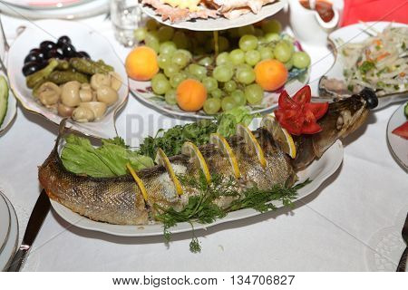 pike perch baked in oven served with lemon on a platter