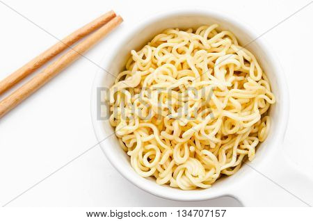 Bowl of instant noodles isolated on white background. Chopsticks.