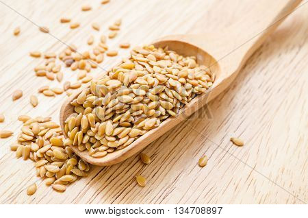 Flax seeds or Linseed close-up in wooden scoop on wooden background.