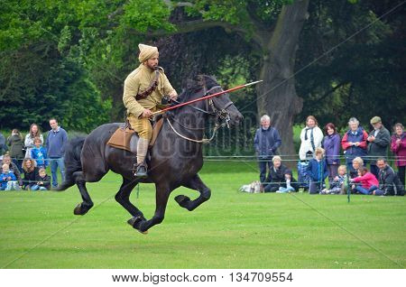 Silsoe, Bedfordshire, England - May 30, 2016: Demonstration of the sport of Tent Pegging at full gallop  by a member of the Punjab Lancers in World War One uniform