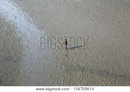 CANNING TOWN, WEST BENGAL, INDIA - FEBRUARY 13: During low tide the water in the river Malta falls so low that people walk to the other shore in Canning Town, India on February 13, 2014.