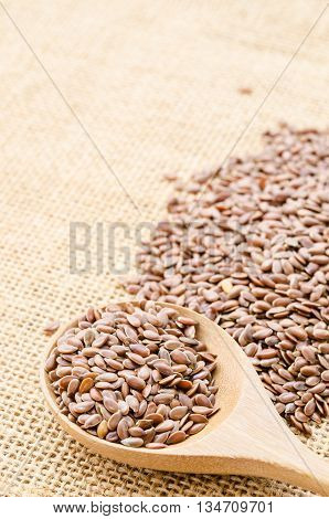 Heap of brown linseed flax seeds with wooden spoon on sack background concept for healthy nutrition