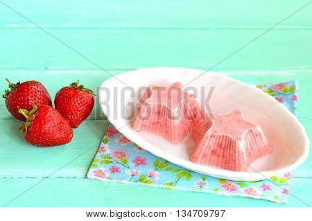 Home pink ice cream shaped star, fresh strawberries. Strawberries mixed with yogurt and sugar and frozen in a freezer. Sweet berry sorbet on a plate