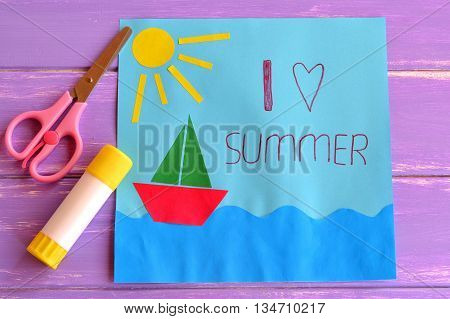 Colorful paper card with ship, sea, sun and words I love summer. Scissors and glue stick on lilac wooden background. Preschool and kindergarten paper crafts. Summer fun background.