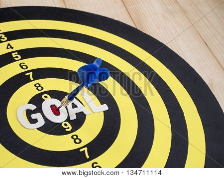 Word spell GOAL on dart board with blue arrow wood background (Selective Focus)