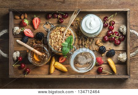 Healthy breakfast ingredients. Oat granola in open glass jar, fruit, yogurt, berries and mint in rustic tray over wooden background, top view