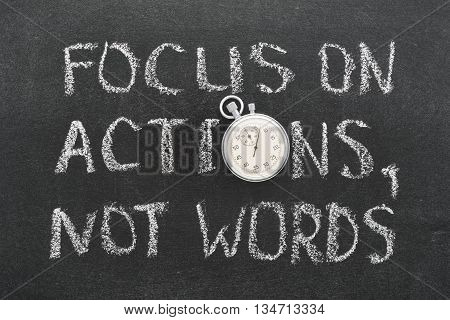 focus on actions not words phrase handwritten on chalkboard with vintage precise stopwatch used instead of O