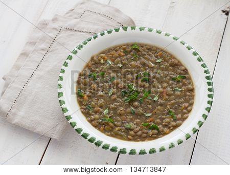 Lentil soup with thyme in a white ceramic bowl on a white wooden surface
