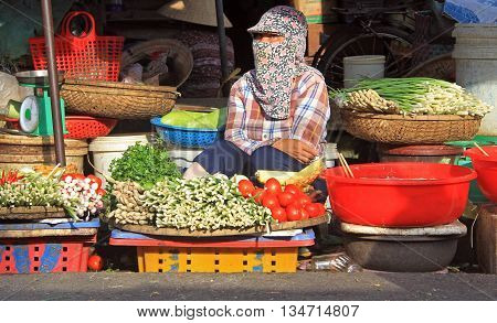 woman is selling vegetables on street market in Hue Vietnam