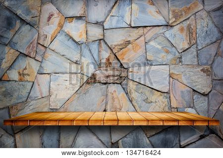 Empty wooden shelf on stone wall background. For display or montage your products.
