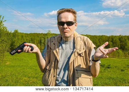 A man with a gun throws up his hands outdoors