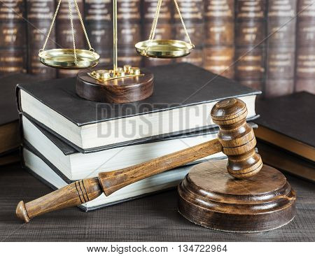 Wood gavel soundblock scales and stack of old books against the background of a row of antique books bound in leather