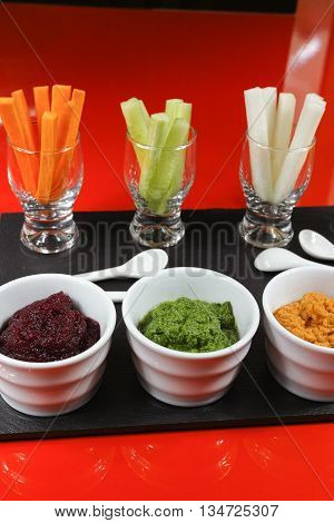 Healthy snacks - colofrul vegetable sticks and mousses on red and black background