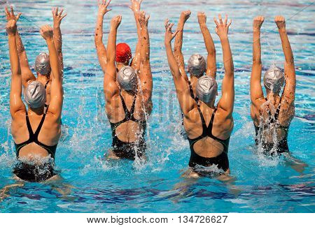 Synchronized swimming team performing a synchronized routine of elaborate moves in the water