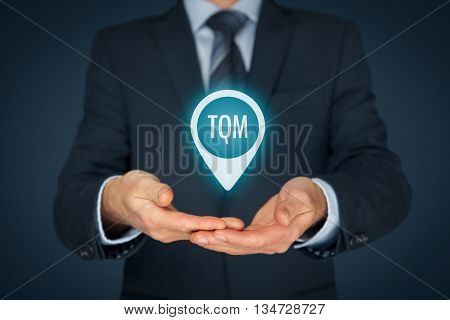 Total quality management concept. TQ manager hold target with text TQM.