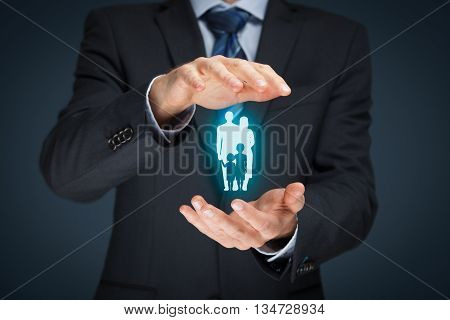 Family life insurance family services and supporting families concepts. Businessman with protective gesture and silhouette representing young family.