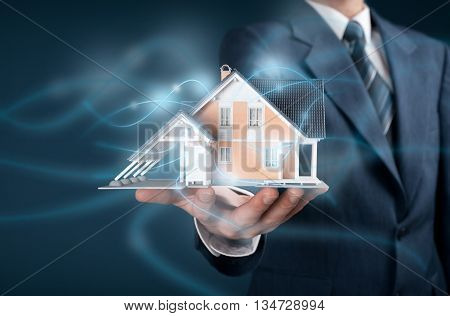 Real estate agent offer intelligent house smart home and home automation concept. Model of the house and wireless communication represented by futuristic graphics.