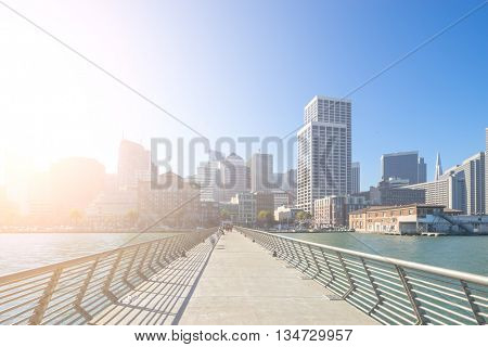 empty footpath over water to modern office buildings in san francisco with sunbeam