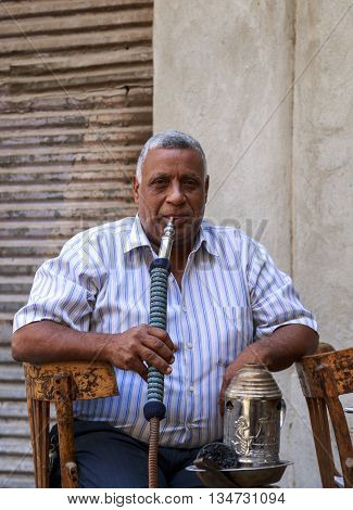 Cairo Egypt - September 26 2015: Friendly Egyptian man sitting outdoor street cafe smoking sheesha water pipe in Islamic Cairo.