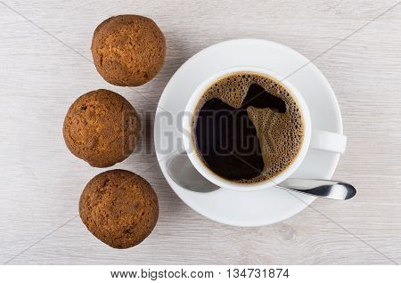 Coffee And Three Muffins On Wooden Table