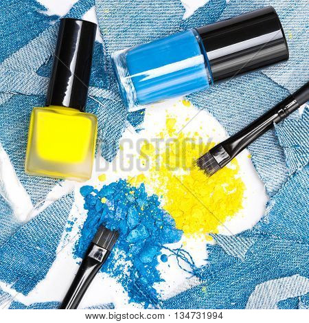 Close-up of makeup brushes, crushed compact blue and yellow eyeshadow with nail polishes of the same colors surrounded by rags of denim. Modern stylish makeup and manicure