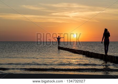 two teenagers balancing on a jetty at sunset