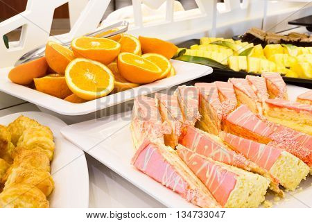 Tray of sliced cake with pink icing on a buffet table with a selection of pastries and fresh sliced fruit in a restaurant or event venue