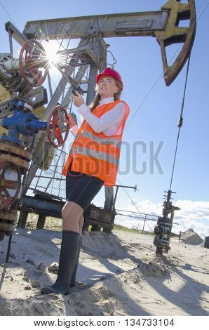 Woman engineer in the oil field talking on the radio wearing red helmet and work clothes. Pump jack and wellhead background. Oil and gas concept.