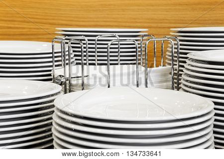 Buffet platters stacked around napkin display and set upon a wooden table