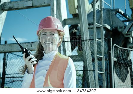 Beautiful woman engineer in the oil field talking on the radio wearing red helmet and work clothes. Pump jack background. Oil and gas concept. Toned.