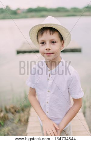 little boy in a white straw hat on the river with wooden bridge