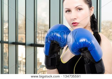 Portrait of a young beautiful woman in boxing gloves in the gym