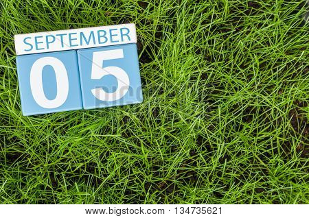 September 5th. Image of september 5 wooden color calendar on green grass lawn background. Autumn day. Empty space for text.