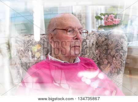 Portrait of 95 years old English man sitting in chair in domestic environment with glass reflection effect. Health and care concept