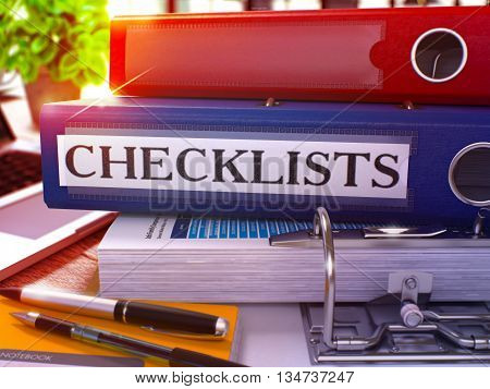 Blue Ring Binder with Inscription Checklists on Background of Working Table with Office Supplies and Laptop. Checklists Business Concept on Blurred Background. 3D Render.