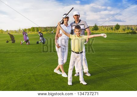 Happy boy golfer plaing golf with parents