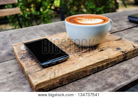 Smartphone With Cup Of Latte Art Milk Coffee Leave Texture On Wooden Background.