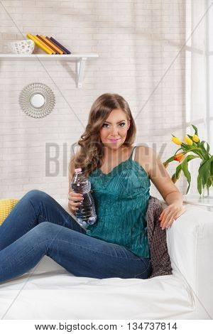 Beautiful happy woman drinking water at home