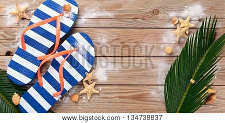 Summer flip flops and seashells on old wooden background.
